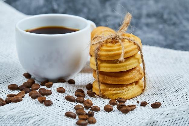 Pile de biscuits avec des grains de café et une tasse de café sur une nappe blanche.