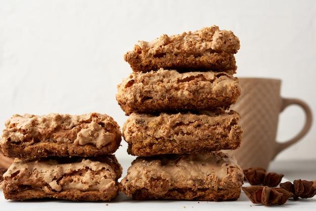 Pile de biscuits meringués cracovie au four sur une planche de bois et une tasse en céramique blanche avec du café noir