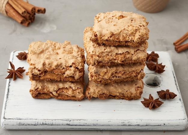 Pile de biscuits meringués cracovie au four sur une planche de bois et tasse en céramique avec du café noir