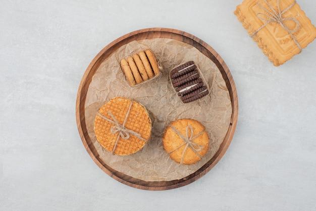 Pile de biscuits de noël attachés avec une corde sur une plaque en bois