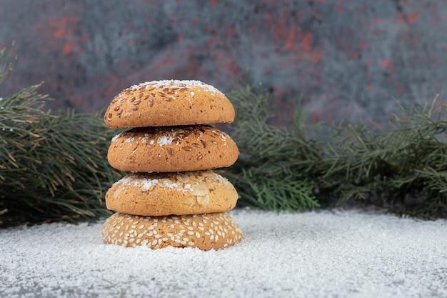 Pile de biscuits placés à côté de branches d'arbres sur une table en marbre.