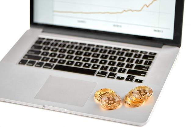 Pile de bitcoins dorés placés sur un ordinateur portable en argent avec graphique financier flou sur son écran.