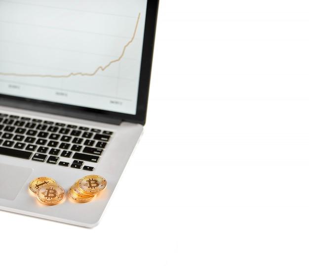 Pile de bitcoins dorés placés sur un ordinateur portable argenté avec tableau financier flou sur son écran