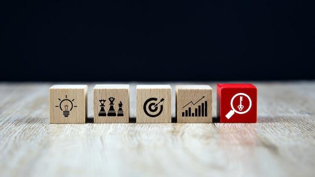 Pile de blocs de bois cube avec la clé sur l'icône de stratégie d'entreprise
