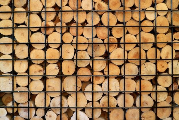 Pile de bois coupé dans une cage en métal pour le fond ou la bannière