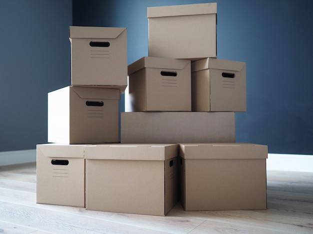 Pile de boîtes en carton debout au milieu de la salle vide dans la nouvelle maison