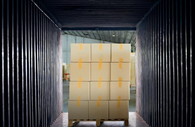 Pile de boîtes en carton sur palette à l'intérieur du conteneur d'expédition