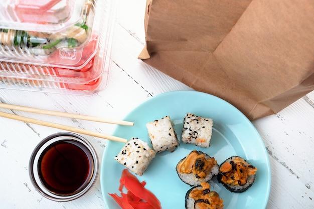 Pile de boîtes en plastique avec des ensembles de rouleaux de sushi, assiette avec des rouleaux et un sac en papier. livraison de nourriture