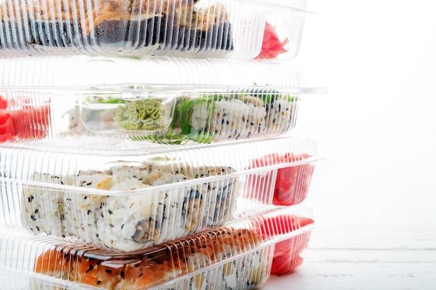 Pile de boîtes en plastique avec des ensembles de rouleaux de sushi. livraison de nourriture