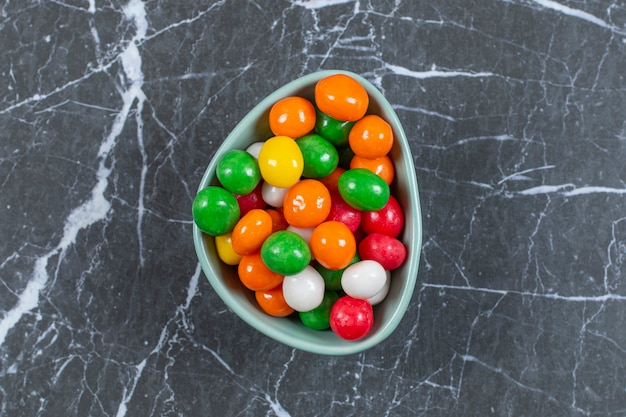 Pile de bonbons colorés dans un bol bleu.