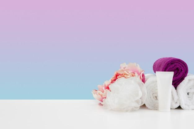 Pile de bouteilles de serviettes avec du shampoing sur une table blanche