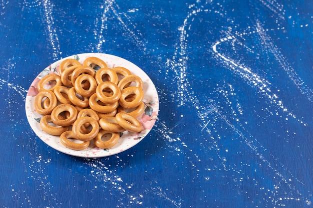 Pile de bretzels ronds salés placés sur une assiette colorée