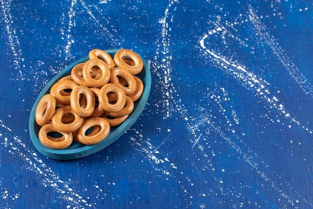 Pile de bretzels ronds salés placés sur une plaque bleue.