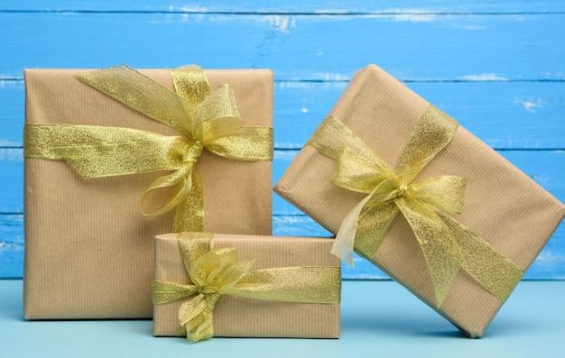 Pile de cadeaux emballés dans du papier kraft brun et attachés avec un ruban doré, boîtes sur fond bleu