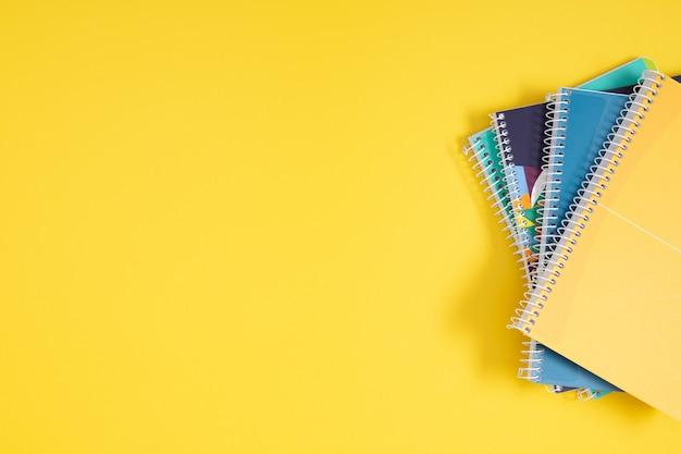 Pile de cahiers colorés sur fond jaune vue de dessus à plat