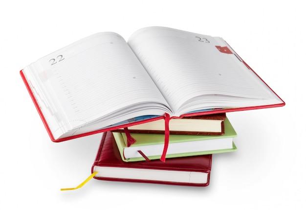 Pile de cahiers avec dessus ouvert rouge