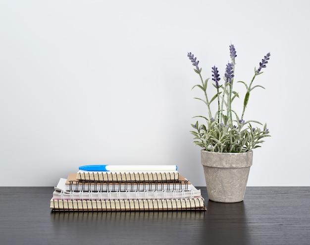 Pile de cahiers à spirale avec des pages blanches et des pots en céramique avec des plantes