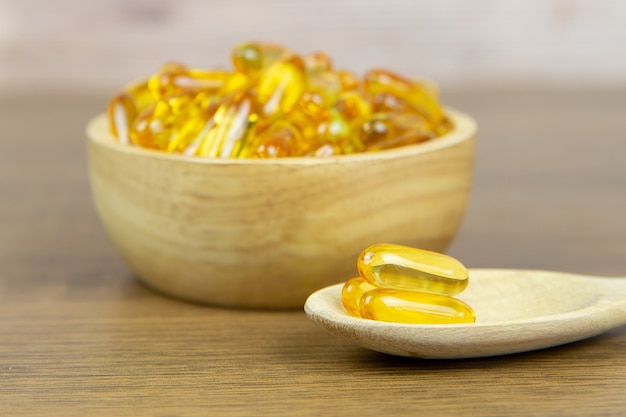 Pile de capsule d'huile de foie de morue dans une cuillère en bois