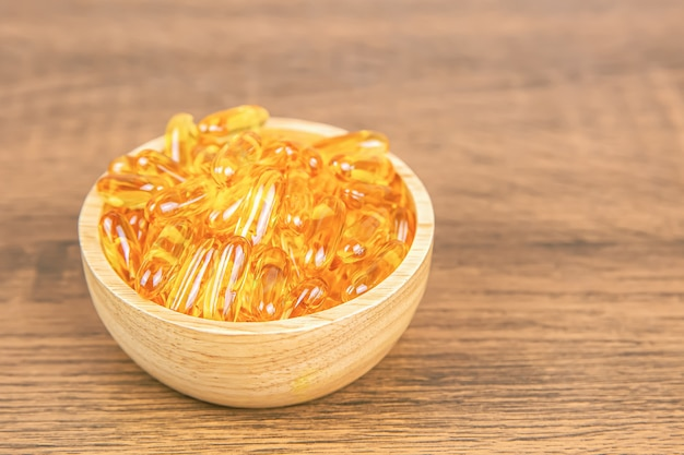 Pile de capsule d'huile de foie de morue dans une tasse en bois