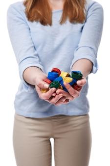 Pile de capsules de bouteilles dans les mains de la femme