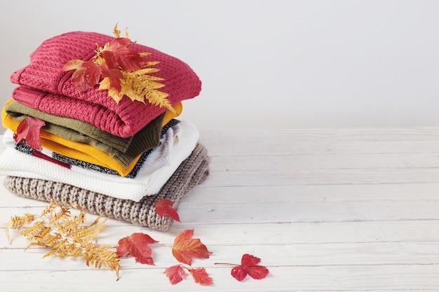 Pile de chandails avec des feuilles d'automne sur une table en bois blanc