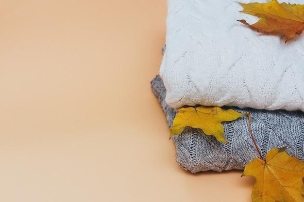 Pile de chandails tricotés chauds avec des feuilles d'automne jaunes concept automne fond beige