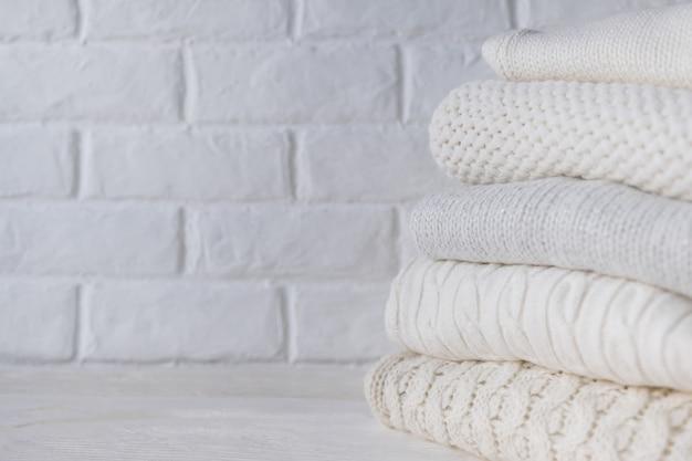Pile de chandails tricotés confortables blancs sur fond de mur de briques blanches.