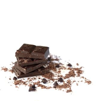 Pile de chocolat noir avec des flocons de chocolat, de la poudre et des gouttes isolés sur une surface blanche