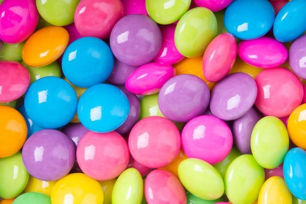 Pile de chocolats sucrés colorés enduits de papier blanc. fond de collection colorée