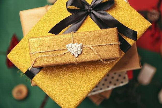 Pile de coffrets cadeaux joliment décorés sur fond de couleur, gros plan