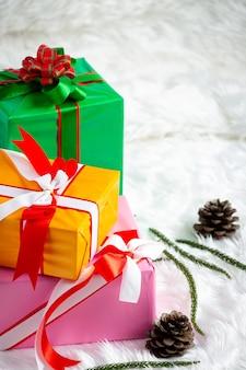 Pile de coffrets cadeaux sur tissu de fourrure blanc