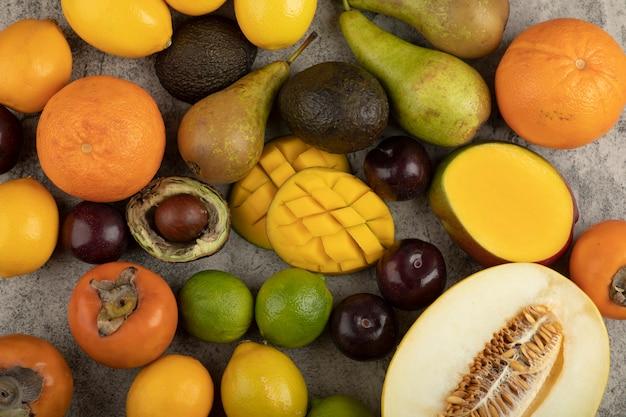 Pile de composition de fruits entiers frais sur une surface en marbre.
