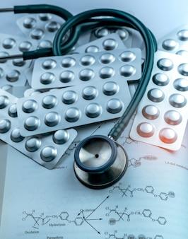 Pile de comprimés comprimés sous blister en aluminium argenté et stéthoscope sur manuel. industrie pharmaceutique. consommation de drogues à l'hôpital. soins de santé.