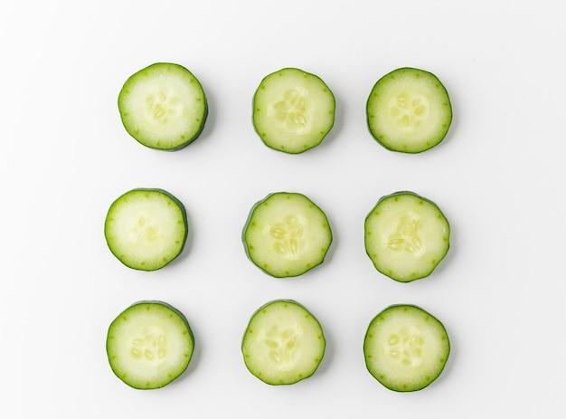Pile de concombre tranché en cercle et disposer sur tableau blanc isolé