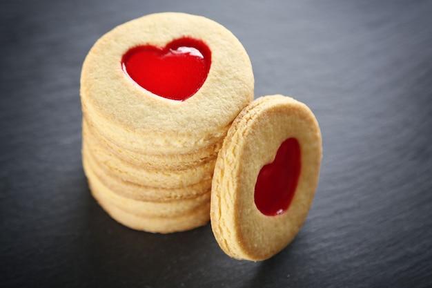 Pile de cookies d'amour sur support gris, gros plan
