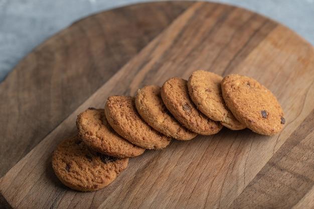 Pile de cookies aux pépites de chocolat sur planche de bois.