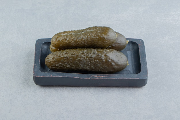 Une pile de cornichons concombre sur une planche, sur la surface en marbre