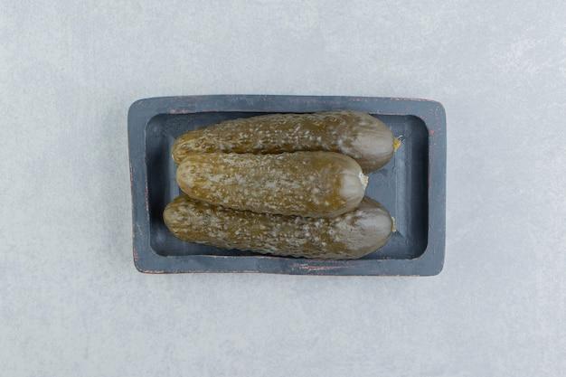 Une pile de cornichons concombre sur une planche
