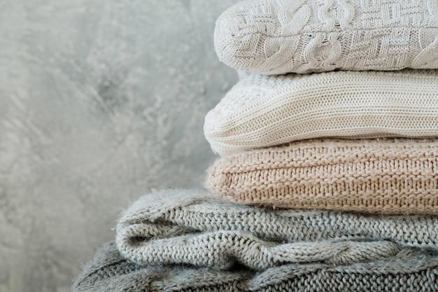 Pile de couvertures et oreillers plaids tricotés confortables pliés. décor à la maison d'hiver chaud et confortable