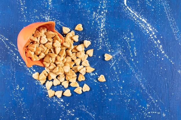 Pile de craquelins salés en forme de coeur placés dans un bol orange.