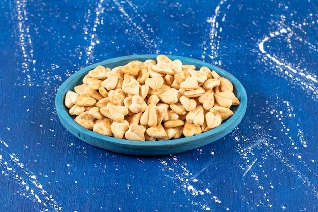 Pile de craquelins salés en forme de coeur placés sur une plaque bleue.