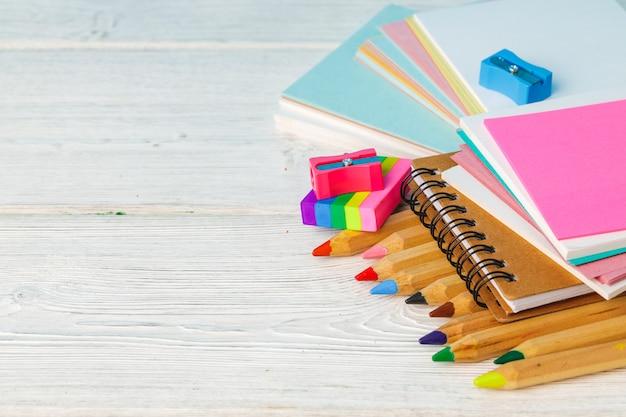 Pile de crayons de couleur et papier sur table en bois