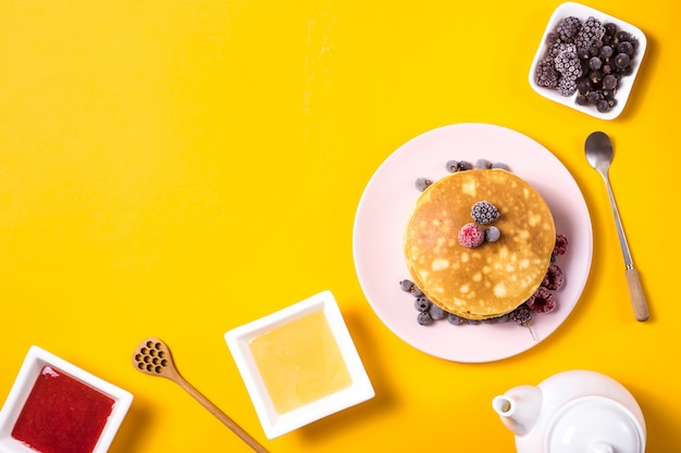 Une pile de crêpes sur une assiette rose avec des baies à côté d'une assiette de miel et de confiture