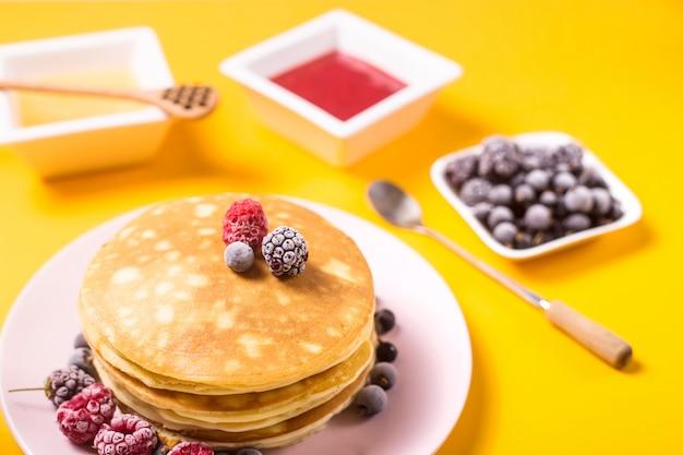 Une pile de crêpes sur une assiette rose avec des baies à côté de miel et de confiture de fraises