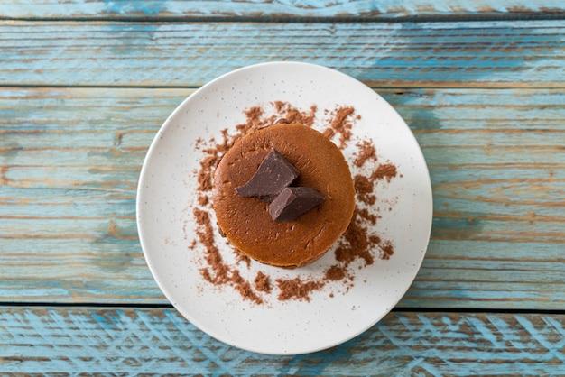 Pile de crêpes au chocolat avec de la poudre de chocolat