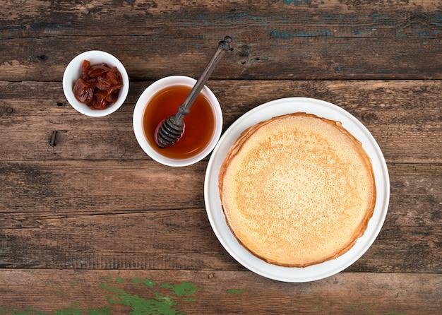 Une pile de crêpes au miel et confiture sur un fond en bois brun.