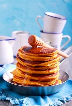 Pile de crêpes au miel dans la poêle