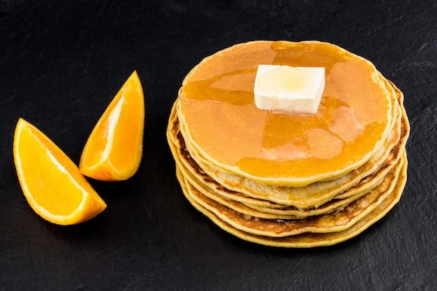 Pile de crêpes au sirop avec des oranges sur fond sombre