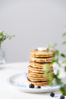 Pile de crêpes aux bleuets, morceau de beurre et miel