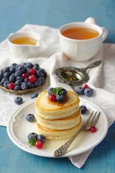 Pile de crêpes avec des baies fraîches et du miel